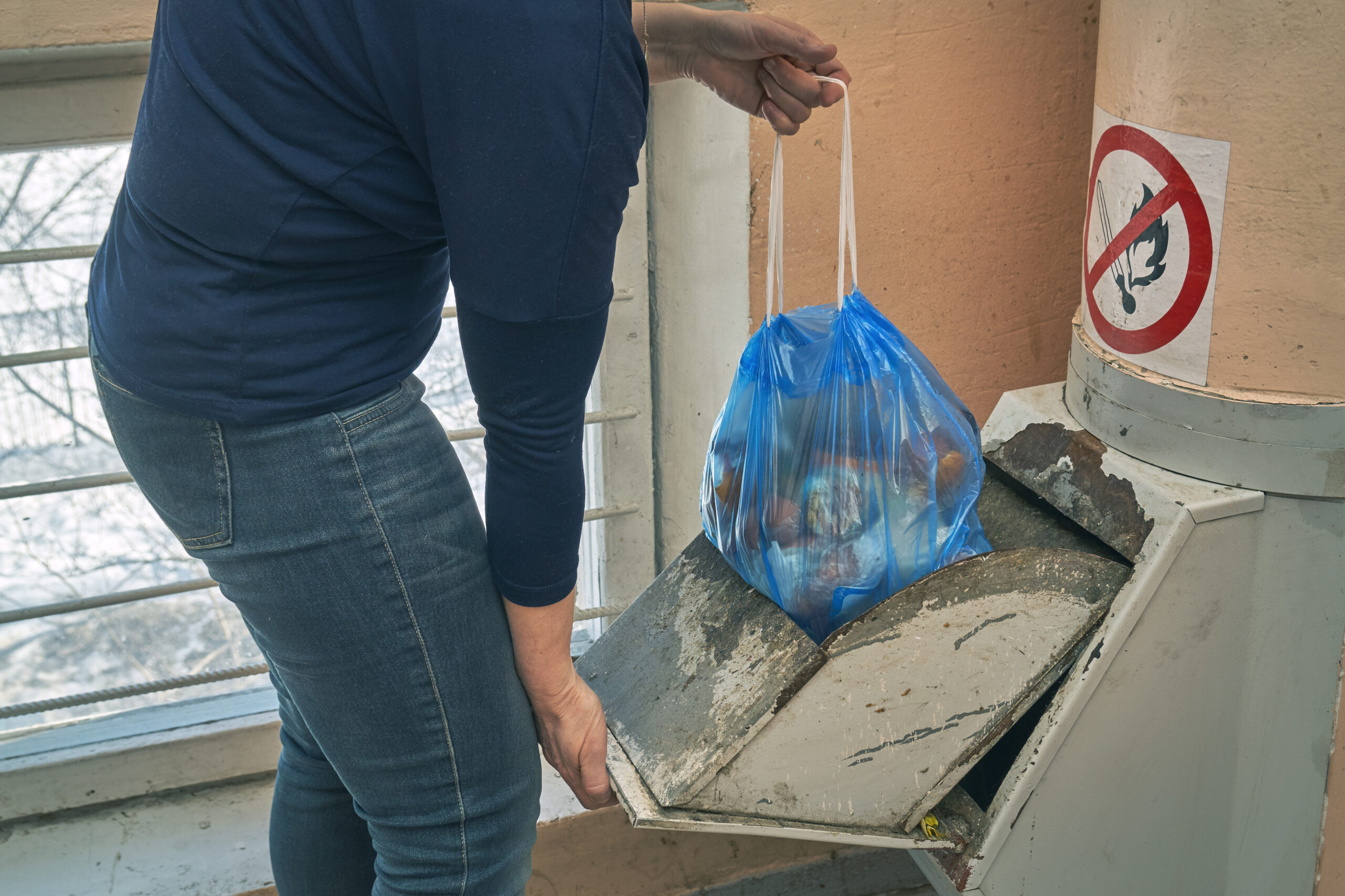 Woman puts a garbage bag in a lid of home garbage chute in Moscow dwelling house
